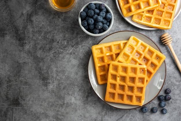 Waffles belgas com mirtilo e mel no café da manhã. deliciosa pastelaria caseira. copie o espaço.