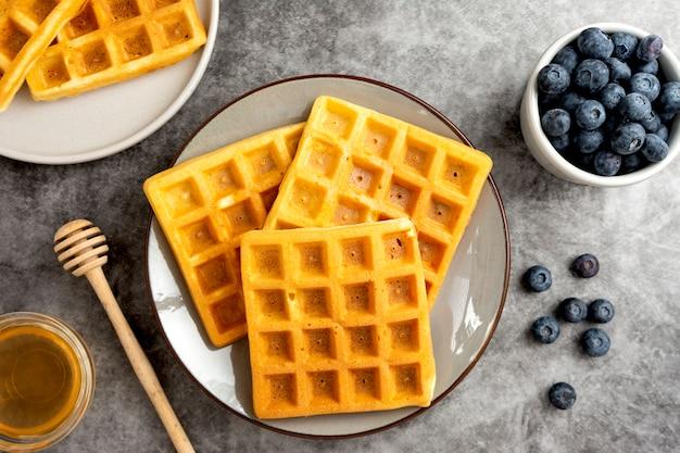Waffles belgas com mirtilo e mel no café da manhã. deliciosa pastelaria caseira.