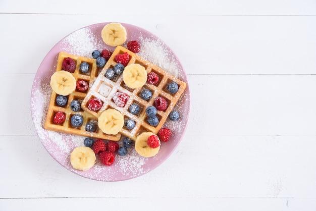 Waffles belgas com mirtilos, framboesas, bananas e açúcar em pó no fundo branco. conceito de comida saborosa e saudável. vista do topo.