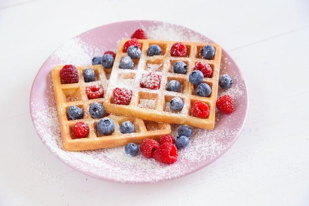 Waffles belgas com mirtilos, framboesas e açúcar em pó. conceito de comida saborosa e saudável.