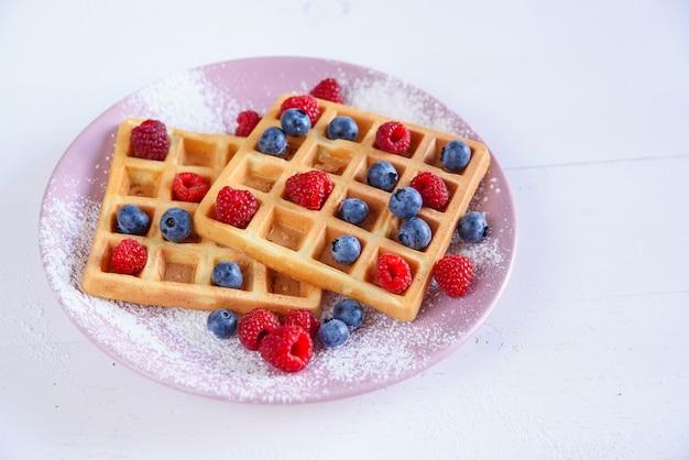 Waffles belgas com mirtilos, framboesas e açúcar em pó no fundo branco. conceito de comida saborosa e saudável.