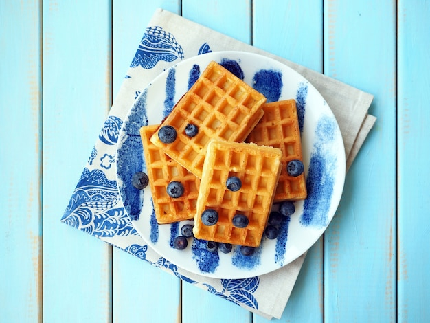 Waffles belgas com mirtilos na mesa azul