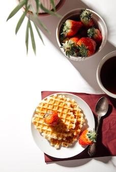 Waffles belgas com morangos em um fundo branco