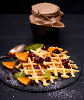 Waffles belgas cozidos com geléia e frutas frescas
