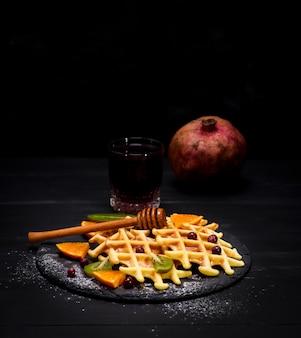 Waffles belgas cozidos e um copo de suco de romã