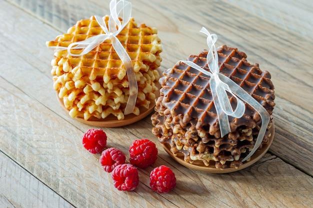 Waffles belgas crocantes frescos com framboesas maduras no café da manhã em uma mesa rústica de madeira.