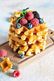 Waffles belgas crocantes frescos no café da manhã com frutas maduras (framboesas, mirtilos, amoras), hortelã e açúcar de confeiteiro em uma placa de madeira sobre um fundo claro.