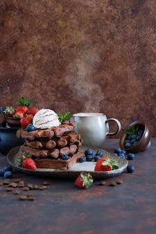 Waffles belgas de chocolate com frutas frescas e sorvete de café em uma placa de cerâmica na mesa marrom