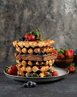 Waffles belgas de chocolate e baunilha com frutas frescas em uma placa de cerâmica