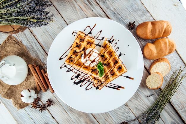 Waffles belgas derramado sorvete de calda de chocolate