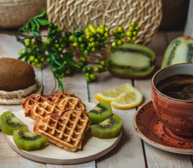 Waffles belgas em forma de coração com fatias de kiwi e uma xícara de café