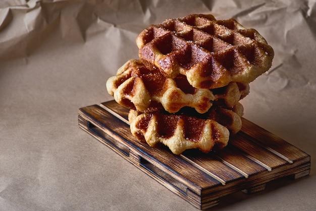 Waffles belgas em papel pardo e bandeja de madeira