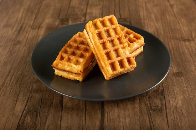 Waffles belgas em um pires em uma mesa de madeira.