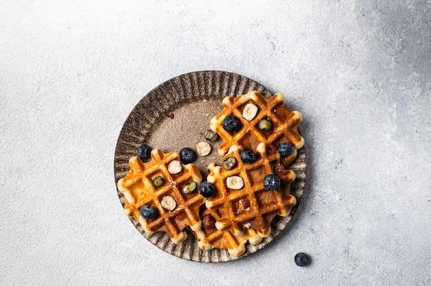 Waffles belgas feitos na hora com mirtilo e avelã. waffles com mel e frutas vermelhas. lugar para texto. copie o espaço. café da manhã doce clássico