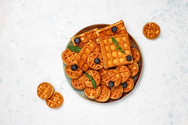 Waffles belgas tradicionais com bagas frescas e mel na superfície de concreto cinza.