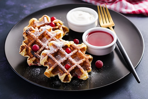 Waffles belgas tradicionais com frutas, creme de leite e geléia na mesa escura.