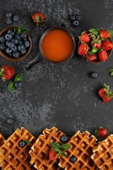 Waffles belgas tradicionais com frutas frescas, mel, coberturas doces e hortelã no escuro