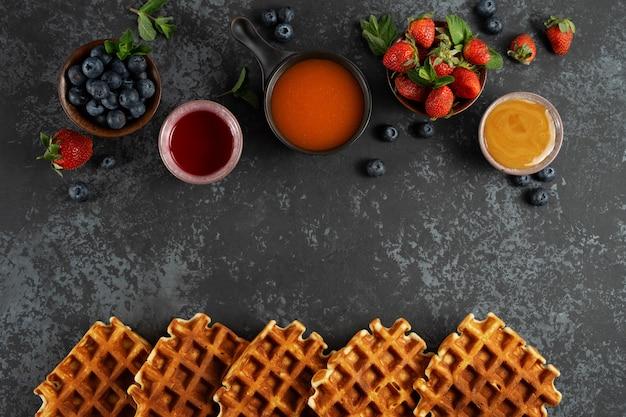 Waffles belgas tradicionais com frutas frescas, mel, coberturas doces e hortelã no fundo escuro
