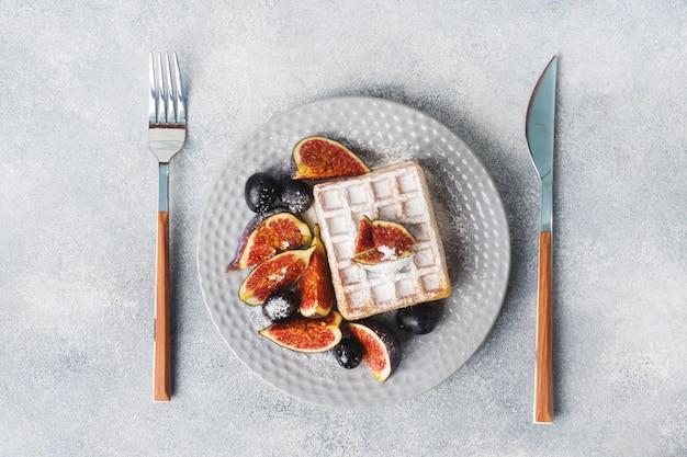 Waffles belgas tradicionais com uvas de açúcar em pó e figos.
