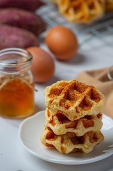 Waffles belgas tradicionais, laranjas pigmentadas e mirtilos, molho e xícara de café no café da manhã doce, composição sobre fundo claro.