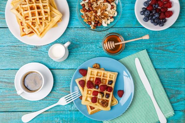 Waffles caseiros com framboesas e mirtilo, xícara de café, leite e talheres