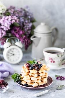 Waffles caseiros com frutas e mel, uma xícara de café na mesa com um buquê de lilases