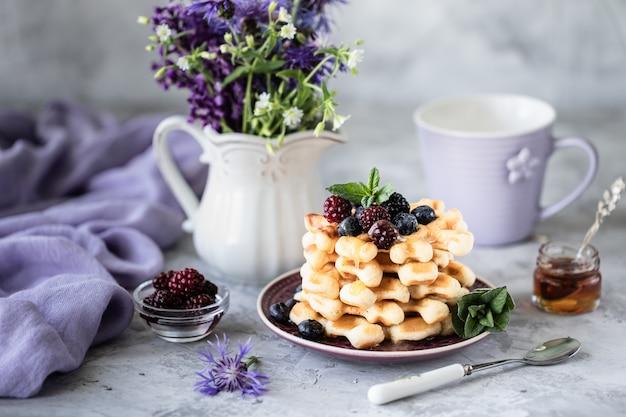 Waffles caseiros com frutas e mel, uma xícara de café na mesa com um buquê de lilases.