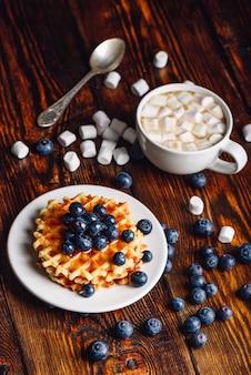 Waffles caseiros com mirtilo fresco e cobertura no prato, xícara de chocolate quente com marshmallow. orientação vertical.