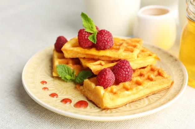 Waffles caseiros doces com framboesas frescas no prato, em superfície clara