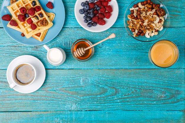 Waffles caseiros, framboesas frescas e mirtilo, xícara de café, leite, nozes e mel.