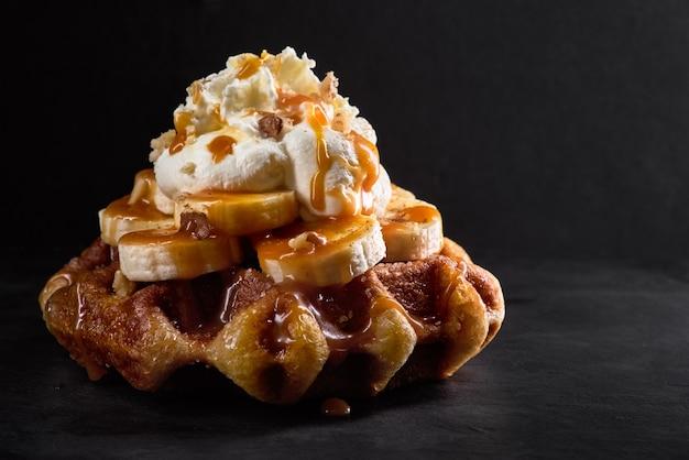 Waffles com bananas cobertos com calda de caramelo em um fundo de pedra escura