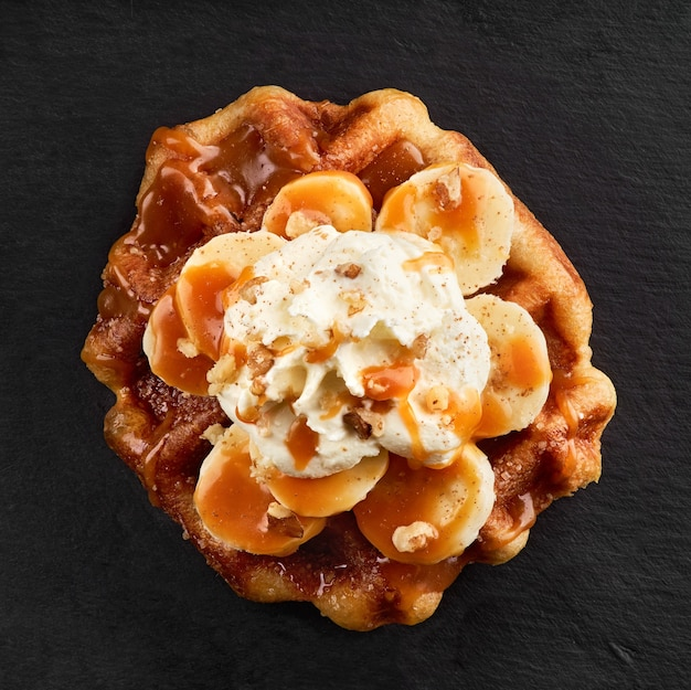 Waffles com bananas cobertos com calda de caramelo em uma superfície de pedra escura. ver topo