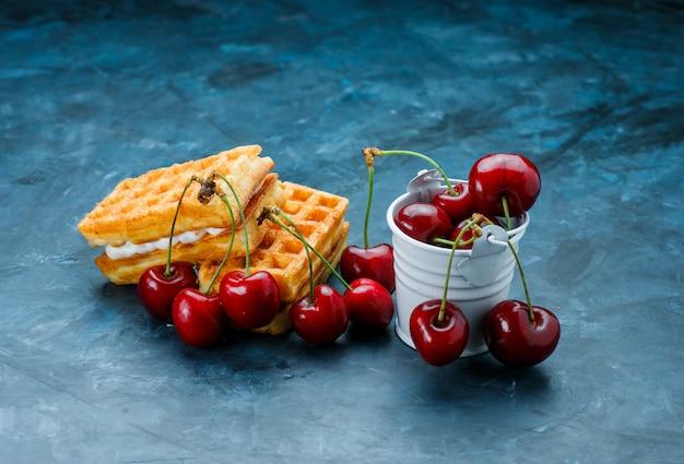 Waffles com cerejas alto ângulo vista sobre uma superfície azul suja