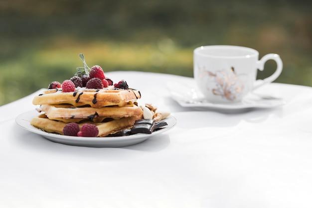 Waffles com coberturas de framboesas na placa e café de cerâmica na mesa branca no exterior