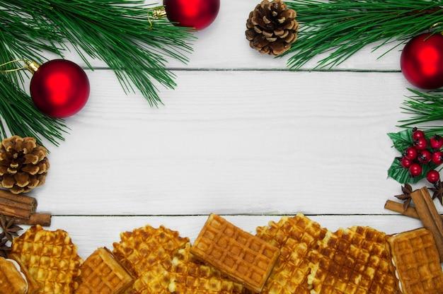 Waffles com estrelas de canela e anis e quadro de árvore de natal de ramo e bola vermelha com cone na superfície vintage de madeira branca