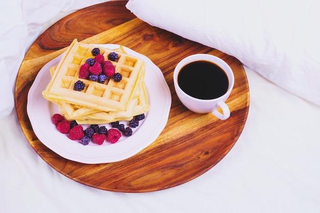 Waffles com frutas e café em uma bandeja de madeira na cama, conceito de café da manhã na cama.