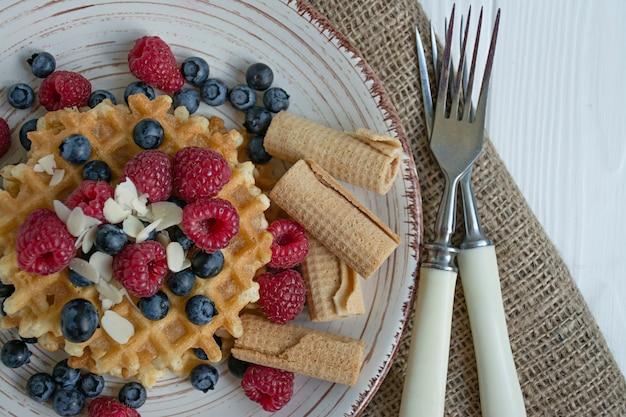 Waffles com frutas frescas no café da manhã. waffles ensolarados. fundo de madeira branco.