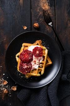Waffles com iogurte e molho de laranja siciliana vermelha na velha superfície de madeira escura. vista do topo.