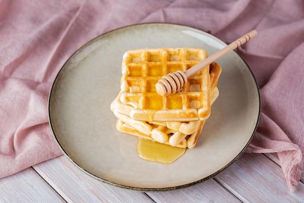 Waffles com mel em um fundo claro