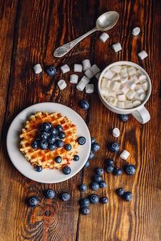 Waffles com mirtilo fresco e mel no prato, xícara de café com marshmallow.