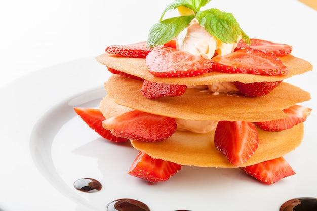 Waffles com molho de caramelo, chantilly e morangos isolados no fundo branco