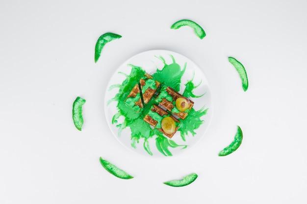 Waffles com molho verde e abacate fatiado, vista de cima.