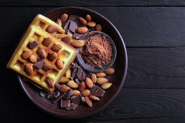 Waffles com vista superior de nozes de chocolate e amêndoas.