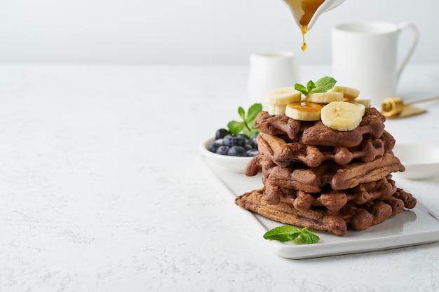 Waffles da banana do chocolate com xarope de bordo na tabela branca, espaço da cópia, vista lateral. brunch doce