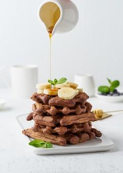 Waffles da banana do chocolate na tabela branca, vista lateral, vertical. brunch doce, xarope de bordo