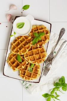 Waffles de abobrinha caseiros com queijo, salsicha e folha de manjericão na mesa branca. conceito de dieta alimentar ceto. foco seletivo.