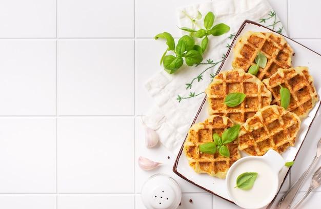 Waffles de abobrinha caseiros com queijo, salsicha e folha de manjericão no fundo branco. conceito de dieta alimentar ceto.