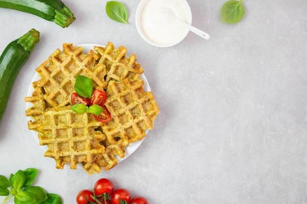 Waffles de abobrinha com queijo, espinafre, tomate, molho de natas e folhas de manjericão em superfície cinza clara