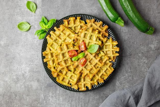 Waffles de abobrinha com queijo, espinafre, tomate, molho de natas e folhas de manjericão em superfície cinza escura