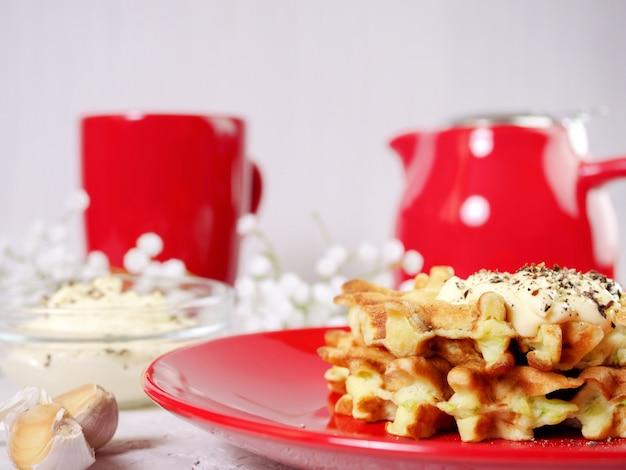 Waffles de abobrinha num prato vermelho com molho e especiarias,